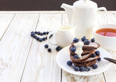 Hot tea and buckwheat chocolate pancakes with blueberries Royalty Free Stock Image