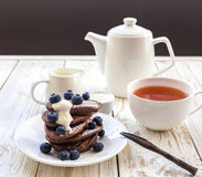 Hot tea and buckwheat chocolate pancakes with blueberries Stock Photography