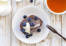 Hot tea and buckwheat chocolate pancakes with blueberries Royalty Free Stock Images