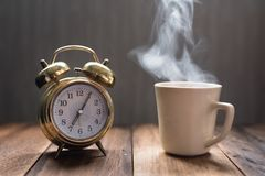 Hot tea / coffee and golden alarm clock on a wooden table stock images