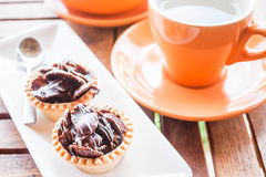 Hot tea and crispy chocolate tarts Stock Photography
