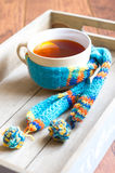 Hot tea. Cup of Hot tea in scarf with cinnamon sticks and lemon Royalty Free Stock Photos