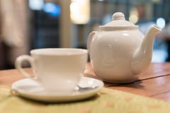 Hot tea cup with spoon on white plate, white kettle, cafe blurred on background, breakfast concept Stock Photo