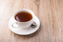 Hot tea cup with spoon. On a wooden table royalty free stock photos