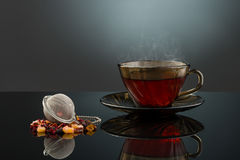 Hot Tea Cup. Steaming forest berry cocktail tea on a glossy surface stock image