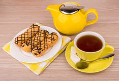 Hot tea in cup, teapot and eclairs on table Royalty Free Stock Photo