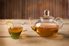 Hot tea cup and a teapot. Hot tea cup with a slice of lemon and a teapot on a wooden table Stock Image
