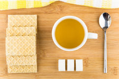 Hot tea in cup wafers, sugar and teaspoon on table Stock Photo