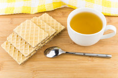 Hot tea in cup wafers and teaspoon on table Stock Photos