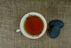 Hot tea cup porselain with relaxing stones on burlap and at black wooden background/Relax moment! Tea time royalty free stock images