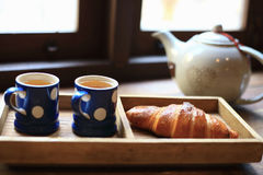 The hot tea in the cups with croissants, as wood background. The hot tea in the cups with croissants, as wood background or print card Stock Image