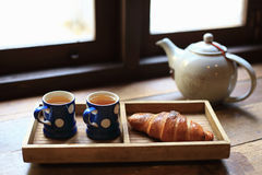 The hot tea in the cups with croissants, as wood background. The hot tea in the cups with croissants, as wood background or print card Royalty Free Stock Photo