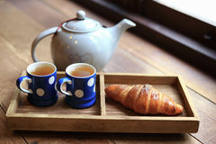 The hot tea in the cups with croissants. The hot tea in the cups with croissants, as wood background or print card Royalty Free Stock Photos