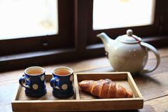 The hot tea in the cups with croissants, as wood background. The hot tea in the cups with croissants, as wood background or print card Stock Photo