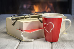 Hot tea by the fireplace. Hot tea, interesting book and the flame of the fireplace warming the heart Royalty Free Stock Photography