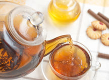 Hot tea flowing from teapot. Into glass mug Royalty Free Stock Photo