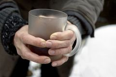 Hot Tea And Frozen Fingers. Tea mug in female fozing fingers, outdoor closeup Royalty Free Stock Photography
