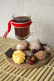 Hot tea in a glass with cookies and chocolate. Hot tea in a glass with cookies, nuts, cranberries and chocolate on a wooden stand Royalty Free Stock Image