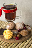 Hot tea in a glass with cookies and chocolate. Hot tea in a glass with cookies, nuts, cranberries and chocolate on a wooden stand Royalty Free Stock Photos