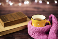 Hot tea, hot chocolate, coffee in yellow cup, wrapped with a pink knitted scarf.  Old books. Blurred lights, wooden background Royalty Free Stock Image