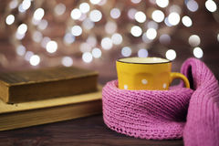 Hot tea, hot chocolate, coffee in yellow cup, wrapped with a pink knitted scarf.  Old books. Blurred lights, wooden background. Winter time, Rustic background Stock Photography