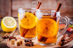 Hot tea with lemon, anise and cinnamon in glass mugs Stock Images