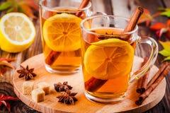 Hot tea with lemon, anise and cinnamon in glass mugs Stock Photos