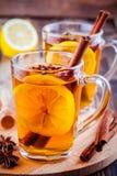 Hot tea with lemon, anise and cinnamon in glass mugs Stock Image