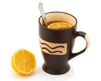 Hot tea with lemon in a black mug Stock Photos