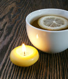 Hot tea with lemon and candle Stock Images