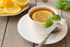 Hot tea with lemon and mint. On woodden table stock images