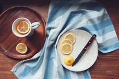 Hot tea with lemon slices on wooden table, top view. Cozy home setting Stock Image