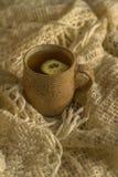 Hot tea with lemon in a vintage mug. On an old blanket stock images