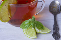 Hot tea with lime in a cup. Hot tea in a cup with lime Pieces and basil Royalty Free Stock Photos