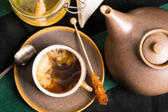 Hot tea with milk. A cup of hot tea on a table with teapot and honey. Milk is mixing with tea Shot from above Royalty Free Stock Image