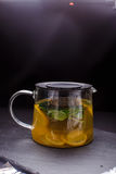 Hot tea with mint and lemon in a glass pot on  black background Royalty Free Stock Images