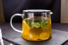 Hot tea with mint and lemon in a glass pot on  black background Stock Photos