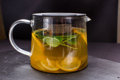 Hot tea with mint and lemon in a glass pot on  black background Stock Image