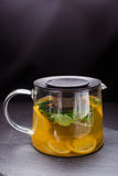 Hot tea with mint and lemon in a glass pot on  black background Stock Photography