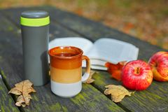 Hot tea, mug, apples and book on a picnic table on a fall day. Vaccuum flask with hot tea, mug, apples and book on a picnic table on a fall day Stock Image