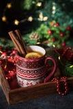 Hot tea near christmas tree. Christmas hot tea with lemon and cinnamon at the table with christmas decoration royalty free stock photos