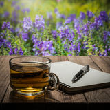 Hot tea with notebook and pen on wooden table Stock Images