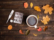 Hot tea, pills, nasal drops, thermometer and autumn leaves on ru Stock Photography