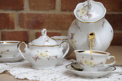 Hot tea in porcelain jug. Hot tea in porcelain jug and antique teacups Stock Image