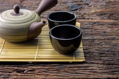 Hot tea pot on bamboo mat with cup on wooden table Stock Images