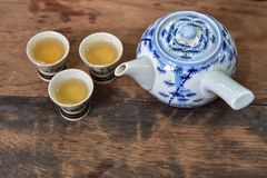 Hot tea pot with three ceramic cups on wooden table Stock Photo