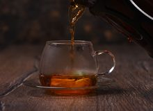 Hot tea is poured into a cup with mint and lemon. Tea is poured into a cup with mint rustic table Royalty Free Stock Image