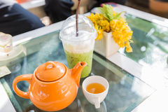 Hot Tea poured into cup with orange pot. My holiday with green tea Stock Photography