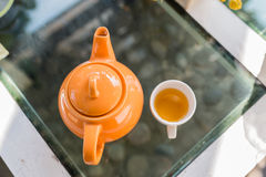 Hot Tea poured into cup with orange pot Stock Photography