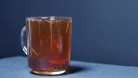 Hot tea is poured into a glass. Transparent glass teapot and teacup. Slow motion stock video
